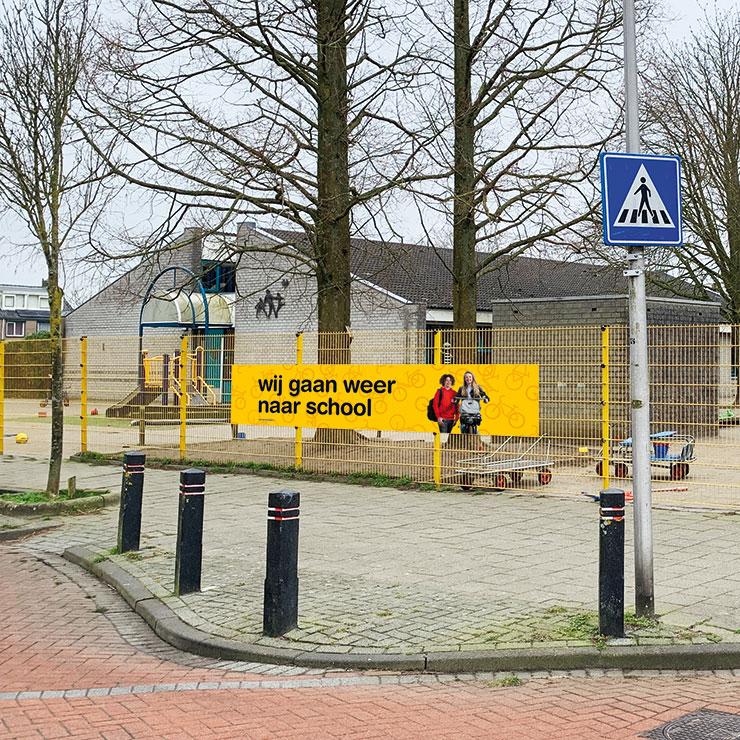 Gele spandoek - 'wij gaan weer naar school' met middelbare scholieren voor veilige start schooljaar. Schoolzones voortgezet onderwijs verkeersveiliger maken.