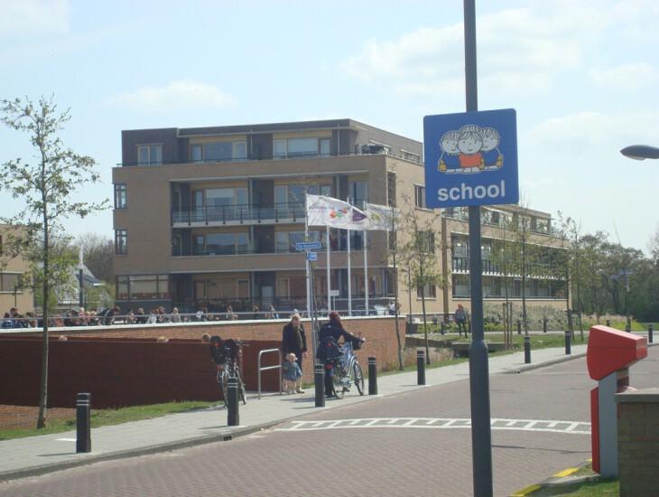 Attentiebord Dick Bruna 'school'. Verkeersbord attendeert weggebruikers op schoolgaande kinderen.